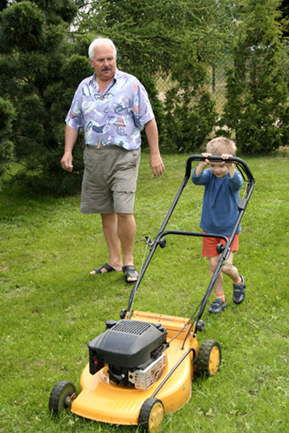 Little Boy Mowing Grass