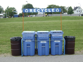 Photo of a special event recycling station with three recycling carts and a banner