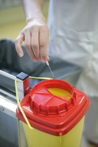 Photo of a hand placing a sharp into the proper disposal container